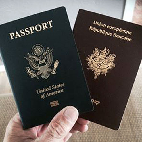 A hand holding two passports from France and the U.S.